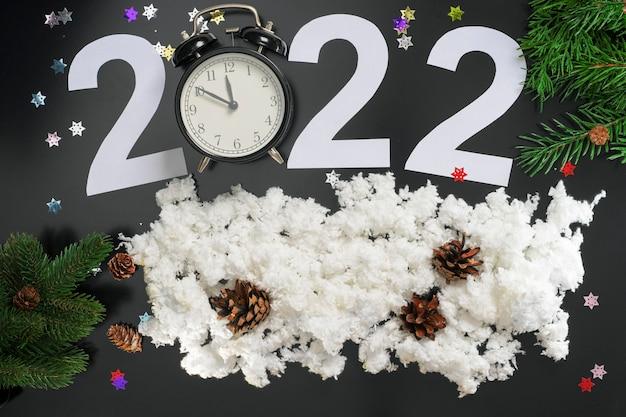 Układ na temat nowego roku 2022 z zegarem, cyframi, gałęziami choinki, śniegiem i zabawkami na ciemnym tle.