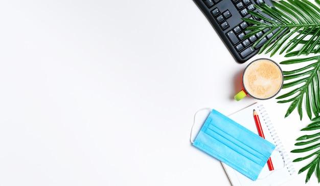 Układ - obszar roboczy z klawiaturą, notatnikiem i filiżanką kawy cappuccino oraz liśćmi kwiatowymi.