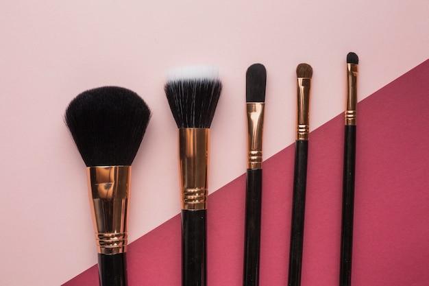 Układ płaski z pędzlami do makijażu i różowym tłem