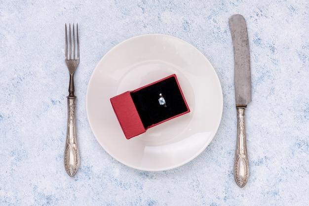 Układ płaski z pierścionkiem zaręczynowym na talerzu