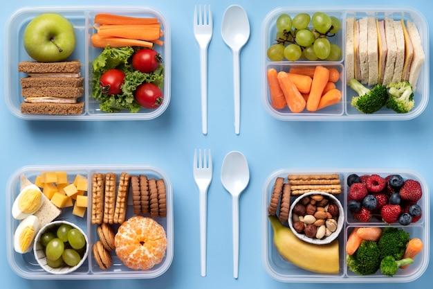 Układ płaskich pudełek na lunch ze zdrową żywnością