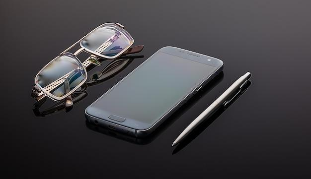 Układ płaskiego, szarego stołu z telefonem na długopis i okularami z miejscem na kopię