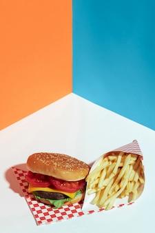Układ pod dużym kątem ze smacznym cheeseburgerem i frytkami