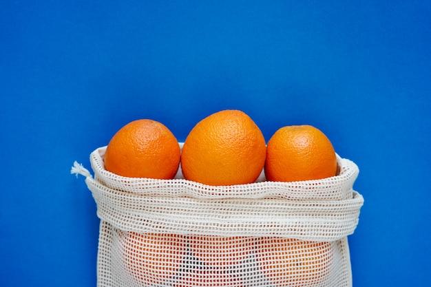 Układ pomarańczy w ekologicznej torbie na niebieskiej ścianie. przyjazny dla środowiska. zatrzymaj plastik, uratuj planetę. widok z góry