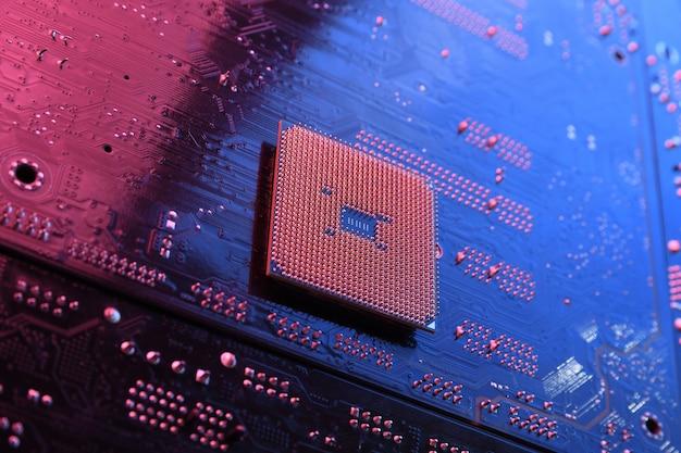 Układ procesora cpu komputera na płytce drukowanej, tło płyty głównej. zbliżenie. z czerwono-niebieskim oświetleniem.