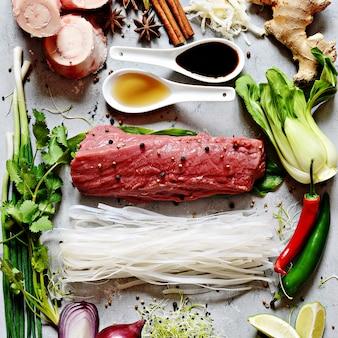 Układ produktów na wietnamskiej zupie pho bo na szarym tle. tradycyjna wietnamska zupa pho bo