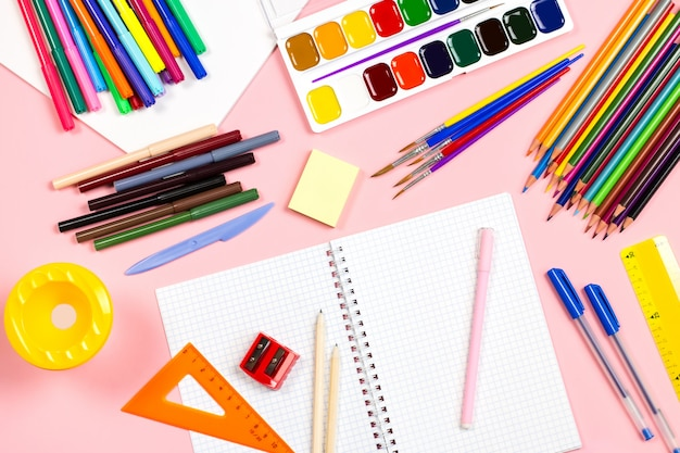 Układ przyborów szkolnych na różowym tle