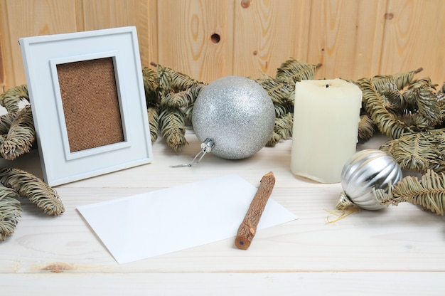 Układ ramki, papieru, ołówka na temat bożonarodzeniowy na białej drewnianej powierzchni