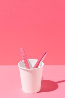 Układ różowych żyletek i kubka