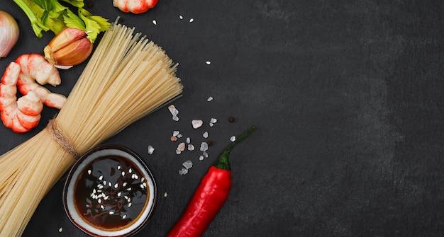 Układ składników do przygotowania smażonego makaronu z krewetkami, owocami morza, sosem sojowym i przyprawami układa się na czarnym kamieniu