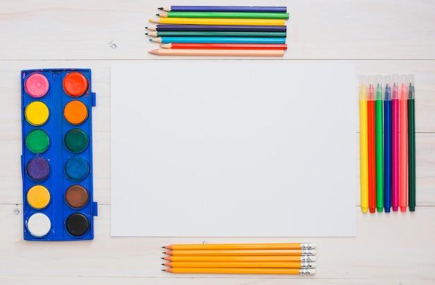 Układ sprzętu do malowania i białego papieru na stole