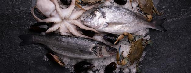 Układ świeżych ryb i owoców morza na marmurowym stole, zdjęcie panoramiczne