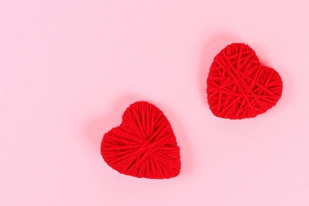 Układ valentine. czerwone, domowe, ręcznie robione serca z tektury i przędzy