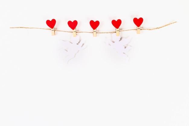Układ valentine. czerwoni serca i biali amorkowie na drewnianych clothespins jutowej dratwie