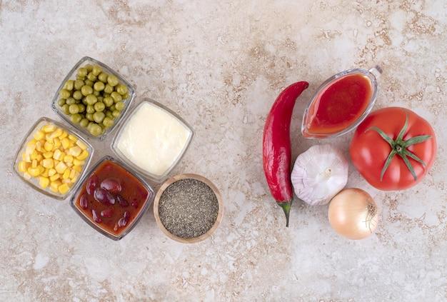 Układ warzyw, dressingów, przypraw i polew na marmurowej powierzchni.