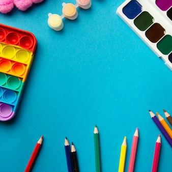Układ widok z góry przedmiotów szkolnych dla dzieci pop to zabawki akwarele kredki na niebieskim tle z miejscem na tekst kolorowe przybory szkolne