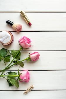 Układ widok z góry z makijażem, różami, spinką do włosów i miejscem na kopię na białym tle drewnianych. koncepcja dnia kobiet, piękna i kobiecości.
