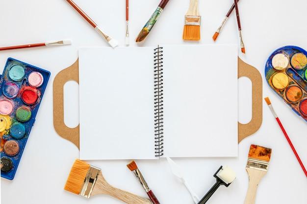 Układ z palety kolorów w pudełku i pustym notesie