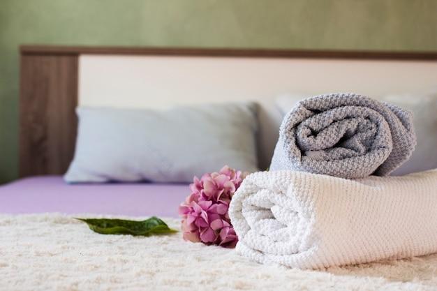 Układ z ręcznikami i kwiatkiem na łóżku