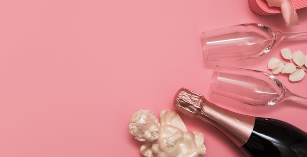 Układ z szampanem, kieliszkami, kupidynem i prezentem na różowym tle z banerem przestrzeni kopii walentynki lub wesele