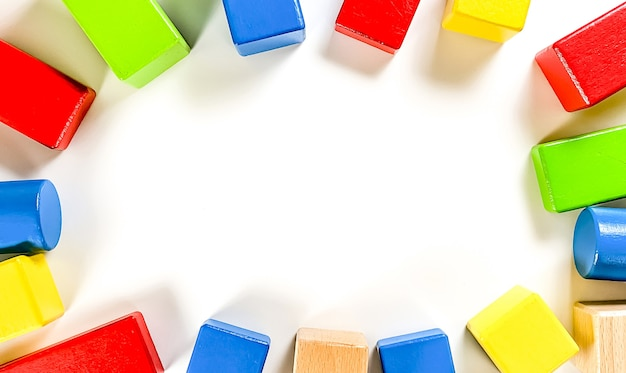 Układ zabawek edukacyjnych dla małych dzieci w postaci wielokolorowych detali konstrukcyjnych na białym tle. koncepcja wczesnego rozwoju dziecka. flatlay, miejsce na tekst.