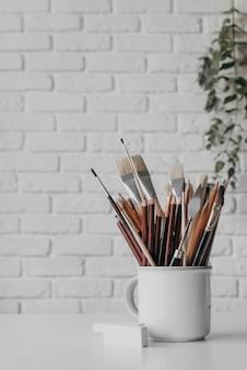 Układ ze szczoteczkami i długopisami w kubku