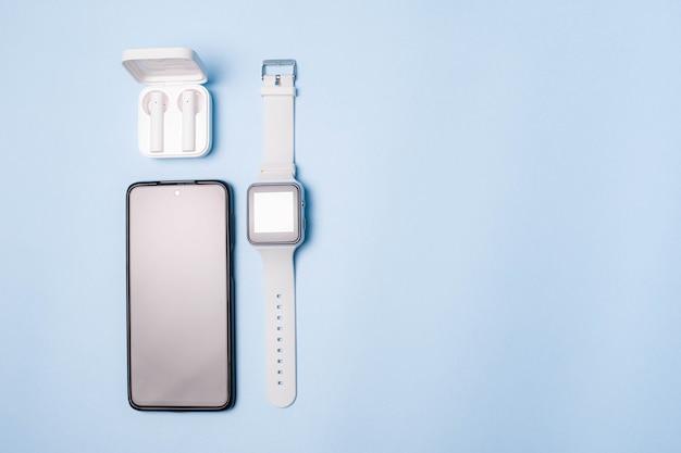 Układ zegarka i telefonu na niebieskim tle. sprzęt agd i elektronika.