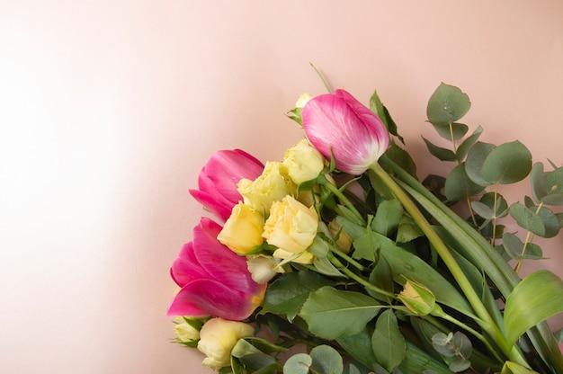 Układania kwiatów płaskich z róż i tulipanów na różowym tle widok z góry