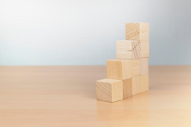 Układanie bloków drewnianych jako schodek. koncepcja ścieżki kariery dla procesu sukcesu firmy