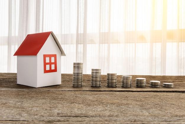 Układanie monet i model domu w celu oszczędzania dzięki rosnącym pieniądzom