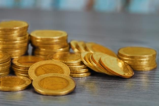 Układanie monet pieniędzy na tle drewna, oszczędność z rosnących pieniędzy.
