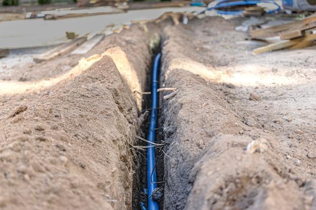Układanie niebieskiego kabla elektrycznego w wykopie w ziemi. komunikacja podziemna. prace elektryczne na budowie.