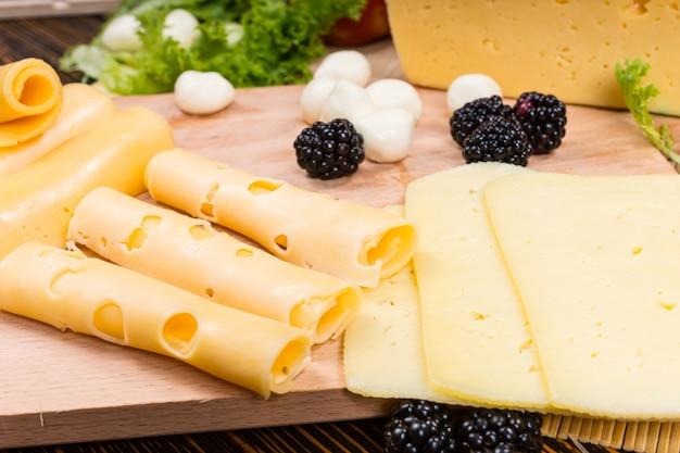 Układanie plastrów bukietu serów na desce serów z rolowanym emmentalem, cheddarem i goudą z mozzarellą i świeżymi jeżynami