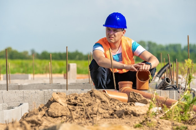 Układanie rur plastikowych do fundamentu budynku.