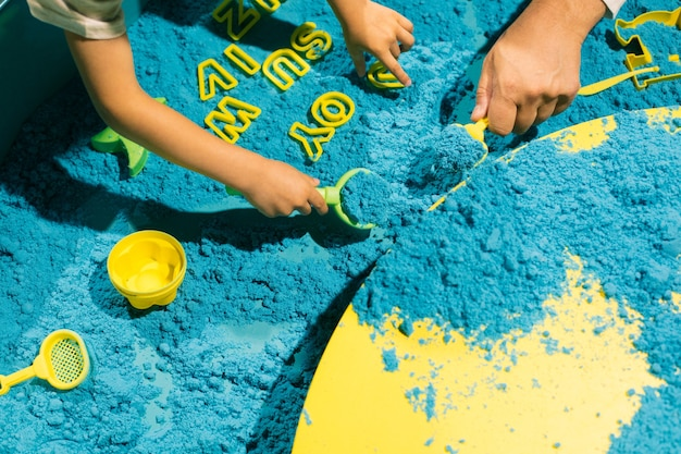 Układanie słów za pomocą niebieskiego piasku kinetycznego. rozwój umiejętności motorycznych. nowoczesne gry edukacyjne. kreatywność i samorealizacja. łagodzenie stresu i napięcia. terapia sztuką.