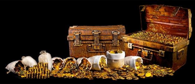 Układanie wielu złotych monet w skrzyni skarbów starych na czarnym tle