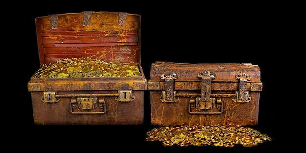 Układanie złotej monety w skrzyni skarbów starej na czarnym tle