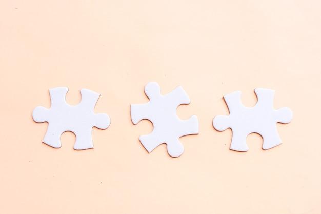 Układanki puzzle nieposortowane elementy na różowym tle
