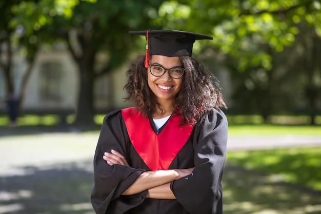 Ukończenie szkoły. całkiem młoda dziewczyna w czapce akademickiej, która cieszy się z ukończenia szkoły