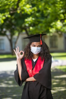 Ukończenie szkoły. ciemnoskóra dziewczyna w akademickiej sukni i masce profilaktycznej