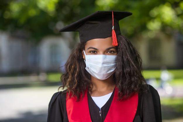 Ukończenie szkoły ciemnoskóra dziewczyna w todze akademickiej i w masce profilaktycznej