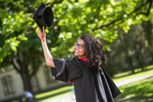 Ukończenie szkoły. ciemnowłosy absolwent czuje się szczęśliwy i podekscytowany ukończeniem