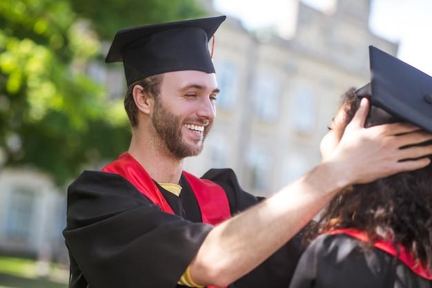 Ukończenie szkoły. dwóch absolwentów czuje się podekscytowanych po ukończeniu studiów i wygląda na szczęśliwych