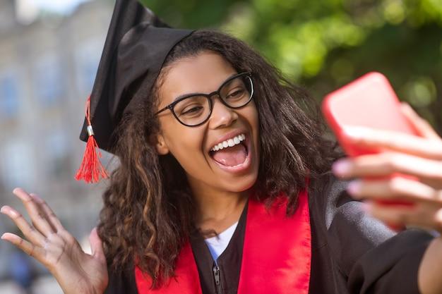Ukończenie szkoły. dziewczyna przeprowadzająca wideorozmowę i dzieląca się dobrą wiadomością o ukończeniu studiów