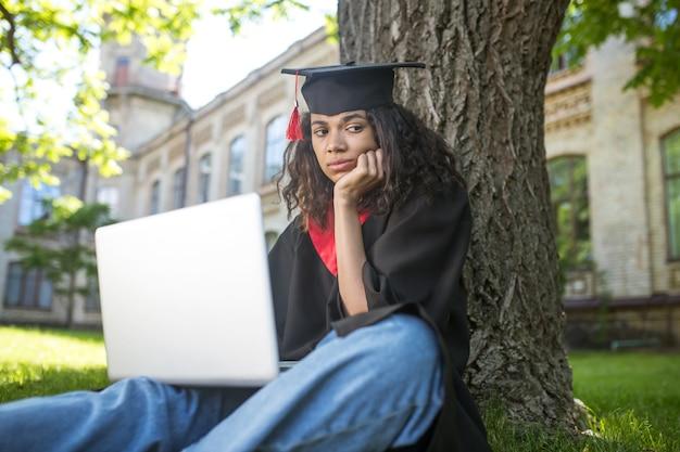 Ukończenie szkoły. dziewczyna w akademickiej sukni siedząca pod drzewem z laptopem