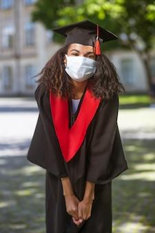 Ukończyć. ciemnoskóra urocza dziewczyna w akademickiej czapce i w masce profilaktycznej
