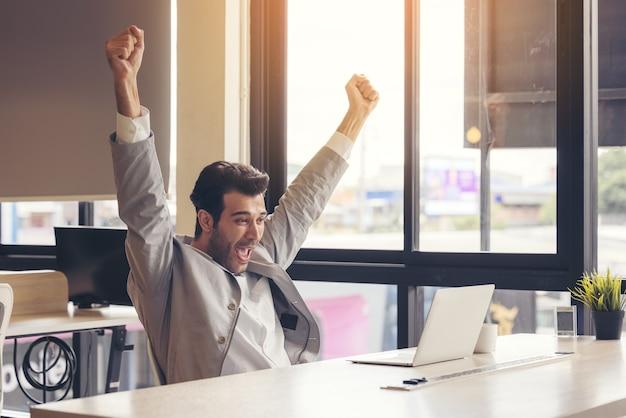 Ukończyłem wyzwanie bardzo zadowolony biznesmen korzysta z laptopa w biurze