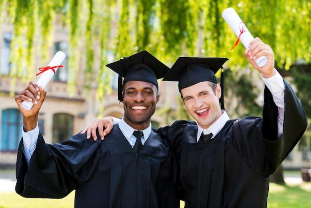 Ukończyli razem. dwóch szczęśliwych młodych mężczyzn w sukniach ukończenia szkoły, trzymających dyplomy i unoszących ręce w górę