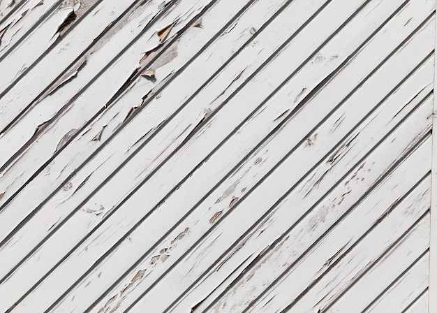 Ukośna linia stodoły wykonana z desek pomalowanych białą farbą, część farby zaczęła odchodzić i wycinać z drzewa