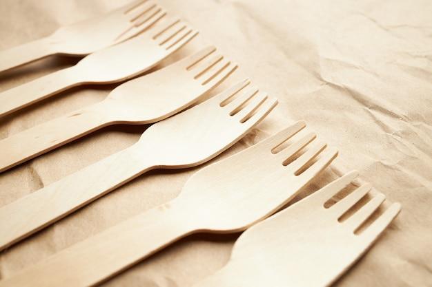 Ukośna linia wykonana przez stos jednorazowych ekologicznych widelców drewnianych na tle papieru. przybory kuchenne. koncepcja przyjazna dla środowiska. miejsce na tekst